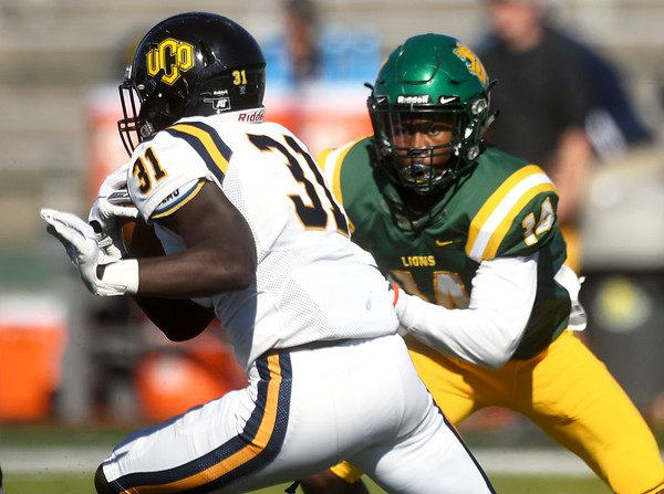 Missouri Southern's Keith Beverly (14) tries to stop Central Oklahoma's Justin Curry (31) during their game on Saturday at Fred G. Hughes Stadium.<br /> Globe   Laurie Sisk