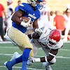 Northeastern Oklahoma A&M runningback Carl Garmon stiff arms Navarro's Carlos Scott to the ground during their game on Saturday night at NEO.<br /> Globe | Laurie Sisk