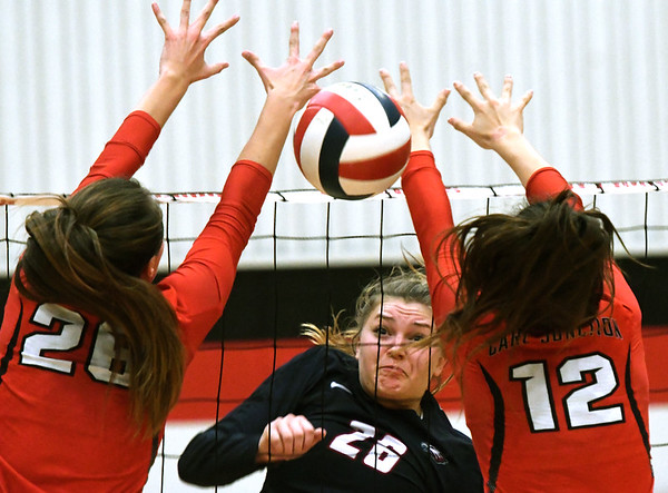 Joplin's Anna Neuenndorf (26) watches her spike split Carl Junction blockers Salma Lewis (26) and Jess Hylton (12) during their match on Tuesday night at CJHS.<br /> Globe | Laurie Sisk