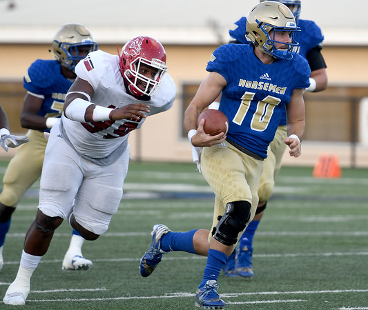 Northeastern Oklahoma A&M rquarterback Clayton Sims (10) gets past Navarro's Jarrus Singleton (99) for a long gain during their game on Saturday night at NEO.<br /> Globe | Laurie Sisk