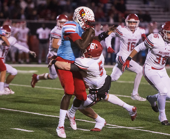 Webb City's Durand Henderson is hit by Carl Junction's Tyler White during Friday's district game in Webb City.<br /> Globe   Roger Nomer