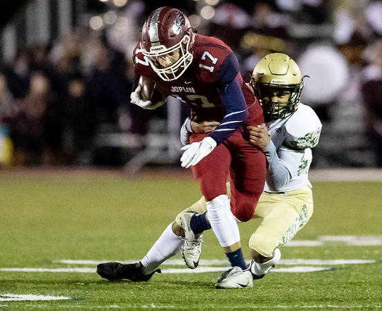 Joplin's Jake Flowers (17) runs the ball as he gets tackle by Anthony Patrick (20) of Lindbergh during their Class 6 District Semifinal game at Junge Field.<br /> Globe Israel Perez