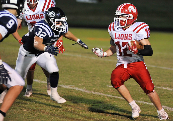 Baxter Springs' Zach Hill carries the ball as Galena's Jacob Whelen (9) and Kooper Lawson (32) make the tackle during Friday's game in Galena.<br /> Globe | Willie Brown