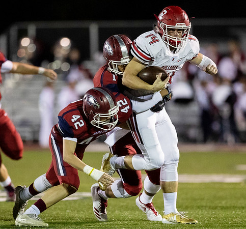 Carl Junction's Joe Kennedy (14) runs the ball as he gets tackle by two of Joplin's defensive line Holden Ledford (42)and Zach Westmoreland (1) during their game on Friday night at Junge Field.<br /> Globe|Israel Perez