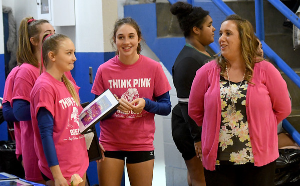 McAuley volleyball coach Amanda Walker visits with some of her players before the start of a game last week at McAuley.<br /> Globe | Laurie Sisk