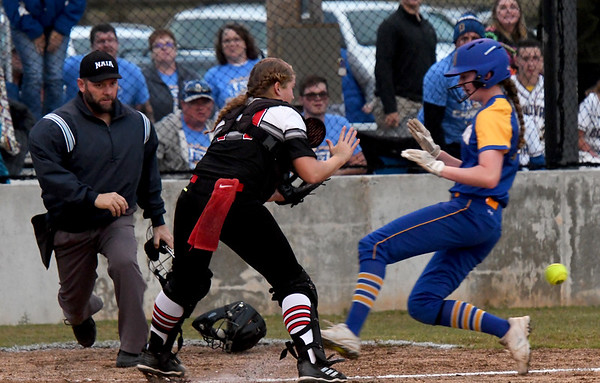 Bolivar's Carsyn Julien (4) beats the throw to home plate for the go-ahead run as McDonald County catcher Kylie Helm (22) fields the throw during their sectional game against Bolivar on Wednesday night at MCHS.<br /> Globe | Laurie Sisk