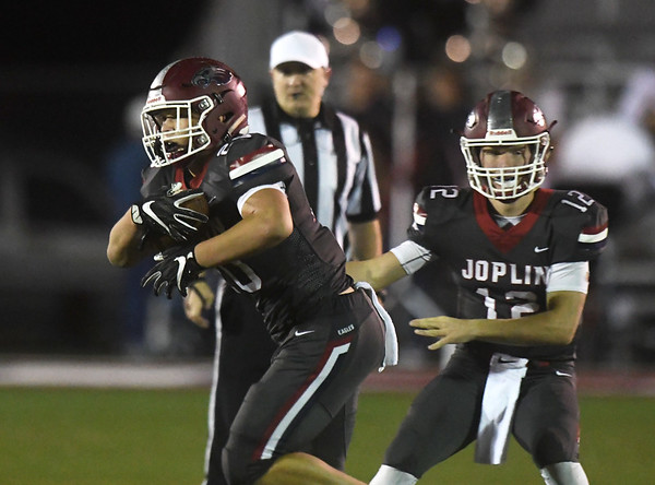 Joplin quarterback Blake Tash (12) hands off to runningback Isaiah Davis (20) for one of the Eagles' eight first quarter touchdowns during their game against Kickapoo on Friday night at Junge Stadium.<br /> Globe | Laurie Sisk