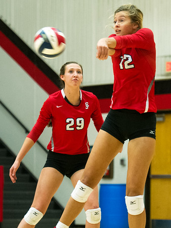 Carl Junction's Olivia Lewis (12) receives a serve as teammate Grace Southern (29) looks on during the Bulldogs' Class 4 District 12 Championship match against Carthage on Wednesday night at CJHS.<br /> Globe | Laurie Sisk