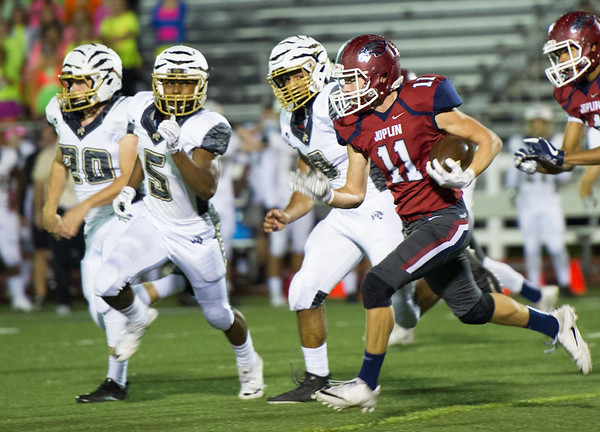 Joplin's Spencer cornet (11) finds room on the outside as Lee's Summit players Austin Spencer (20,) Micah Manning (5) and Victor Hochstetler (8) pursue during their game on Friday night at Junge Field.<br /> Globe | Laurie Sisk