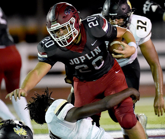 Joplin's Isaiah Davis (20)  tries to get past Neosho's Sam Cook during their game on Friday night at Junge Stadium. Also pictured is Neosho's Drayke Perry (32) .<br /> Globe | Laurie SIsk