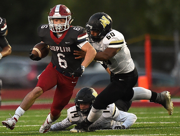 Joplin's Nathan Glades (6) tries to get past Neosho's Drsj Roby (60) during their game on Friday night at Junge Stadium. Also pictured is Neosho's Quincey Willis (14) .<br /> Globe | Laurie SIsk