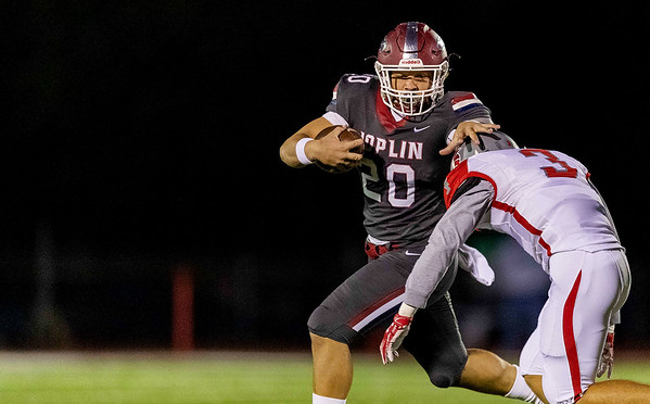 Joplin's Isaiah Davis (20) runs the ball and stiff-arm Nixa's defender Jared Spence during their Senior Night game on Friday evening at Junge Field in Joplin.<br /> Globe|Israel Perez