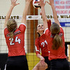 Webb City's Maddy Peeples (21) trtries to get a spike past Carl Junction's Maggie Brown (24) and Logan Jones (8) ) during the championship game of the Class 4 District 11 tournament on Tuesday night at Neosho High School.<br /> Globe | Laurie Sisk