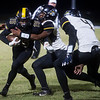 Diamond's Kolbe Jones is tackled by Pleasant Hope's Kameron Price (66) and Marcus Price (4) during Friday's game in Diamond.<br /> Globe | Roger Nomer