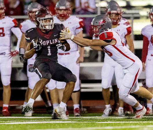 Joplin's Zach Westmoreland runs the ball near the sidelines as he works to break the tackle of Nixa's Michael Sportsman during their Senior Night game on Friday at Junge Field in Joplin.<br /> Globe|Israel Perez