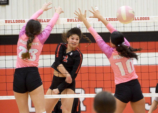 Carl Junction's Jess Hylton (12) watches her spike as he gets past Webb City's Anna Swearengen (23) and Taylyn Smith (10) during their match on Tuesday night at CJHS.<br /> Globe | Laurie SIsk