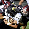 Joplin's Simeon Barba (22) and Scott Lowe (18) combine to bring down Neosho quarterback Gage Kelley (1) during their game on Friday night at Junge Stadium. Also pictured is Neosho's Quincey Willis (14) .<br /> Globe | Laurie SIsk