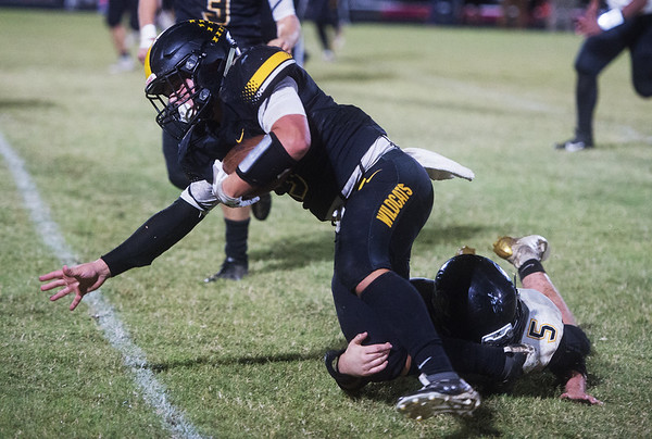 Diamond's Landon Clement is tripped up by Pleasant Hope's Eugene Makara during Friday's game in Diamond.<br /> Globe | Roger Nomer