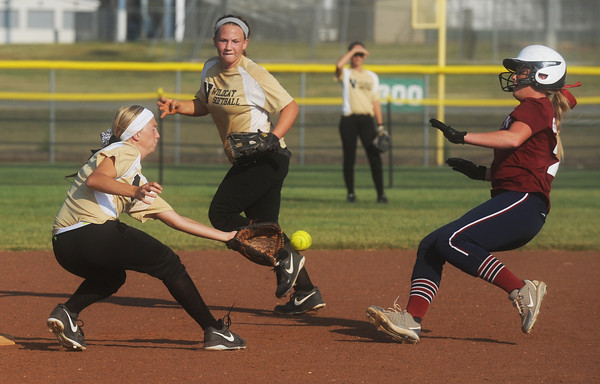 Globe/Roger Nomer<br /> Neosho's Kylie Bach gets the ball in time to tag Joplin's Jessica Greninger as teammate Cassie Dickens looks on during Wednesday's game.