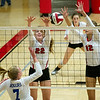 Carl Junction's Sylvia Lawson (22) and Olivia Lewis (12) block a spike from Rogers' Kassidy Wall (7) during pool play at the Dr. Jeffrey Knutzen CJ Classic on Saturday at Carl Junction. Backing up the play is Carl Junction's Kenzie Stinnett.  <br /> Globe | Laurie Sisk