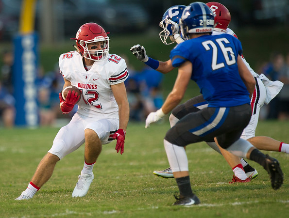 Carl Junction's Michael Elbert (12) looks for running room on a punt return as Carthage's Logan Kobance (26)  during their game on Friday night at Carthage.<br /> Globe | Laurie Sisk