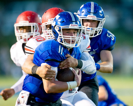 Carthage quarterback Keith Guest II (11) tries to escape from the grasp of Carl Junction defensive end James Fauvergue (30) during their game on Friday night at Carthage.<br /> Globe | Laurie Sisk