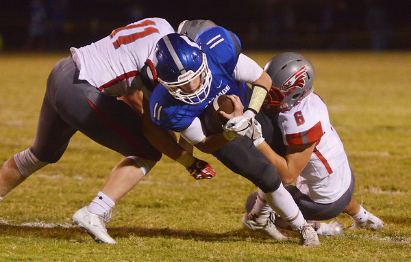Globe/Roger Nomer<br /> Carthage's Keith Guest II fights for yardage against Nixa's Brendon Beckley (11) and Mason Simmons (6) during Friday's game in Carthage.