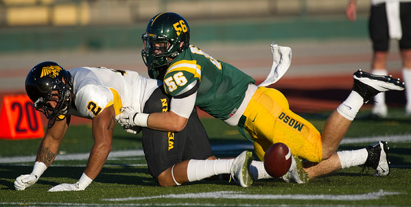 Missouri Southern linebacker Trevor Plafcan (56) forces a fumble from Missouri Western runningback Kendall Short (2) during their game on Saturday night at Fred G. Hughes Stadium.<br /> Globe | Laurie Sisk