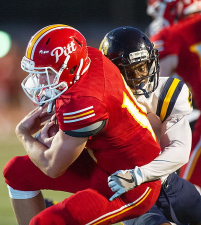 Pittsburg State quarterback Thomas LePage works to elude the tackle of Central Oklahoma defensive back Stephan Robinson (4) during their game on Saturday night at Pittsburg.<br /> Globe | Laurie Sisk