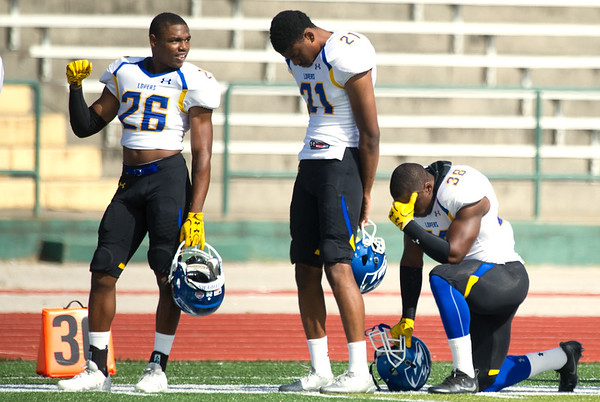 Nebraska-Kearney players Jamarius Harris (26) , Count-Marquis Pippin II (21) and Fred Wortham (38) opt for three different stances during the playing of the National Anthem before the start of their game against Missouri Southern on Saturday at Fred G. Hughes Stadium.<br /> Globe | Laurie Sisk