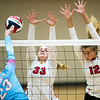 Webb City's Anna Swearengen (23) tries to spike the ball past Carl Junction's Catherine Whelan (33) and Olivia Lewis (12) during their match on Tuesday night at Webb City.<br /> Globe | Laurie Sisk