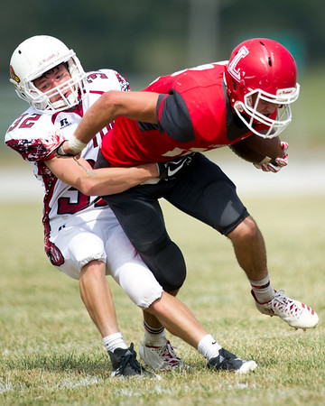 Tipton linebacker Cameron Whisler (32) tries to bring down Liberal receiver Sean Clark (12) during their game on Saturday afternoon at Liberal.<br /> Globe | Laurie Sisk