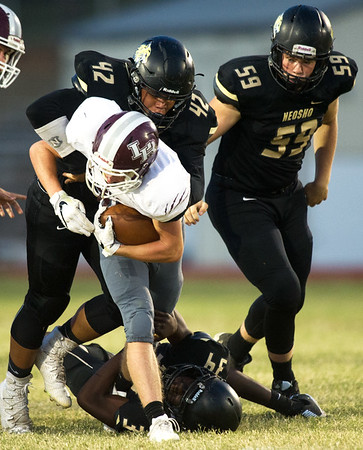 Neosho's Tre Letts (42) and Sam Cook (34) bring down Logan-Rogersville runningback Brooks Wilson (20 as Sean Moran (59) closes in during their game on Friday night at Neosho.<br /> Globe | Laurie Sisk