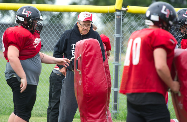 Former state champion coach Mike Rader works with linemen as an assistant coach to his son, Luke Rader on Wednesday at Lockwood High School. Some of the players the senior Rader coaches are grandsons of players he formerly coached.<br /> Globe | Laurie Sisk