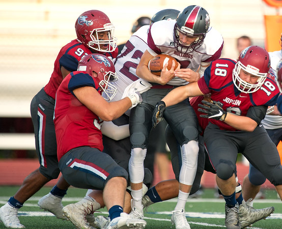 From the left: Joplin defenders Travis Stirewalt (90,) Evan Bernot (92) and Jacob Bartlett (18) swarm Rolla quarterback Josh Pritchett (7) during their game on Friday night at Junge Field.<br /> Globe | Laurie Sisk