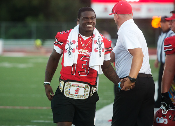 Carl Junction's Rayquion Weston wears the Carl Junction belt as he walks the sidelines on Friday during the game against Willard.<br /> Globe | Roger Nomer