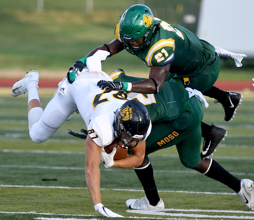 Fort Hays State's Harley Hazlett (87) dives for extra yards as Missouri Southern's Akel Beard (21) and Deshon Cowling (2) defend during their game on Saturday night at MSSU.<br /> Globe   Laurie Sisk