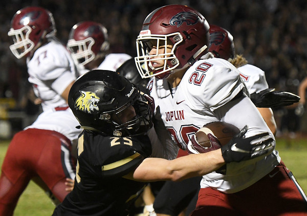 Joplin runningback Isaiah Davis (20) tries to get past Neosho's Cade Lyerla (25) during their game on Friday night at Neosho.<br /> Globe | Laurie Sisk