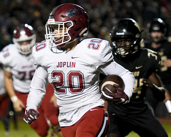 Joplin runningback Isaiah Davis (20) looks for room upfield as Neosho's Sam Cook (34) pursues during their game on Friday night at Neosho.<br /> Globe | Laurie Sisk
