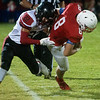 Lamar's Isaac Collins tackles Seneca's Daythen Long during Friday's game in Seneca.<br /> Globe | Roger Nomer
