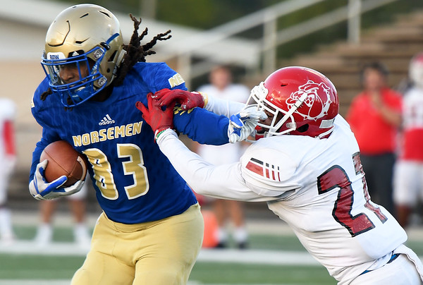 Northeastern Oklahoma A&M receiver Tariq Bitson (83) breaks free for a first quarter touchdown Navarro's Eryk Preston (27) defends during their game on Saturday night at NEO.<br /> Globe | Laurie Sisk