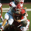 Carl Junction's Joe Kennedy is tackled by Nixa's Taylor Cheek (58) and Logan Ayers (45) during Friday's game in Carl Junction.<br /> Globe | Roger Nomer