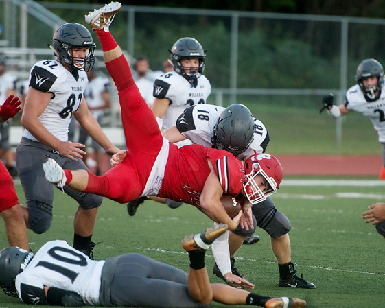 Carl Junction's Joe Kennedy leaps over Willard's Eli Aye (10) for extra yardage as he's tackled by Austin Joplin during Friday's game in Carl Junction.<br /> Globe | Roger Nomer