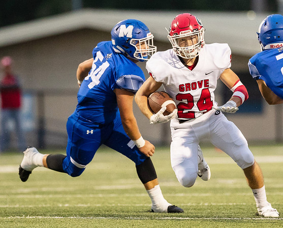 Grove's Kadian Forbis (24) runs the ball as he gets past Hunter Hartman (54) of Miami OK during their game on Friday evening at the Red Robertson Field in Miami OK.<br /> Globe | Israel Perez