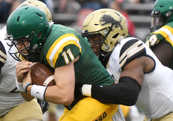 Missouri Southern quarterback Sean Kelly (11) tries to escape the grasp of Lindenwood's CJ Bivens during the Lions home opener on Saturday at Fred G. Hughes Stadium.<br /> Globe | Laurie Sisk