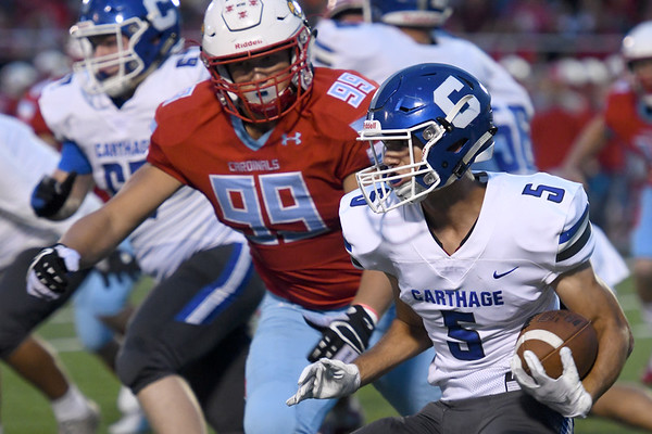 Carthage running back Blake Schrader (5) looks for an opening as Webb City's Trenten Thompson (99) gives chase during their game on Friday night at Cardinal Stadium.<br /> Globe | Laurie Sisk