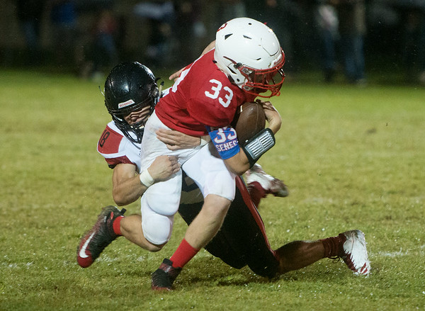 Seneca's Preston Armstrong is tackled by Lamar's Dylan Hill during Friday's game in Seneca.<br /> Globe | Roger Nomer