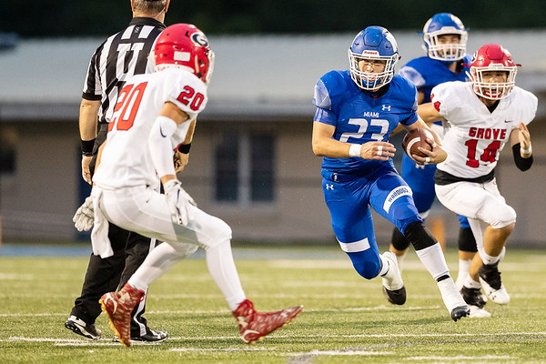 Miami's Caden Folks (23) runs the ball as he looks for a way past Grove's defender Jonas Chaney (20) during their game on Friday evening at the Red Robertson Field in Miami OK.<br /> Globe   Israel Perez
