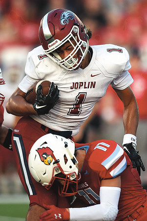 Joplin's Zach Westmoreland (1) holds onto the ball after a hard hit from Webb City's Treghan Parker (11) during their game on Saturday night at Webb City.<br /> Globe | Laurie Sisk