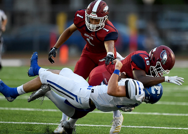 Joplin's Lonnie Watkins (16) brings down Carthgae runningback Tyler Mueller (22) as Zach Westmoreland (1) closes in during their game on Friday night at Junge Field.<br /> Globe | Laurie Sisk